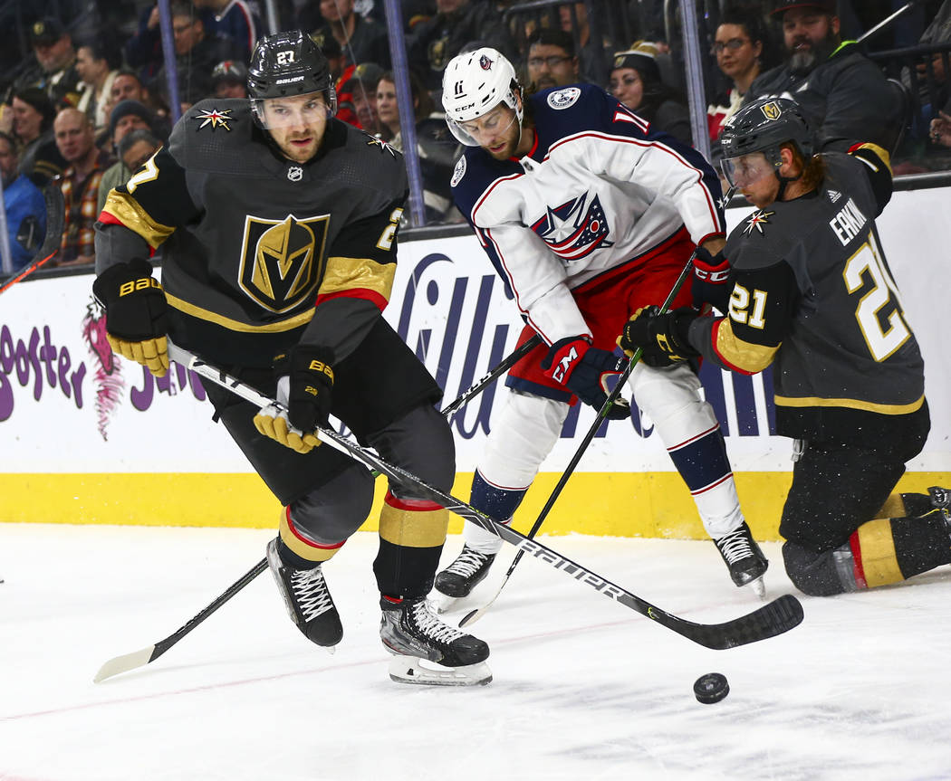 Golden Knights' Shea Theodore (27) skates with the puck past Columbus Blue Jackets' Kevin Stenl ...