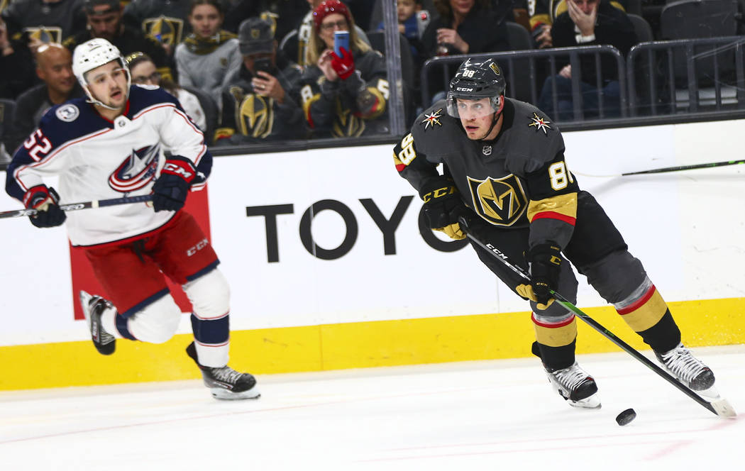 Golden Knights' Nate Schmidt (88) skates with the puck in front of Columbus Blue Jackets' Emil ...