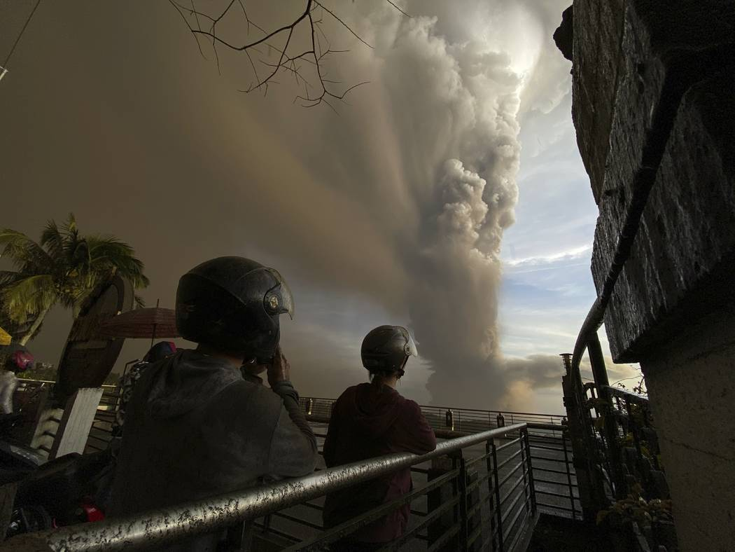 People watch plumes of smoke and ash rise from as Taal Volcano erupts Sunday Jan. 12, 2020, in ...