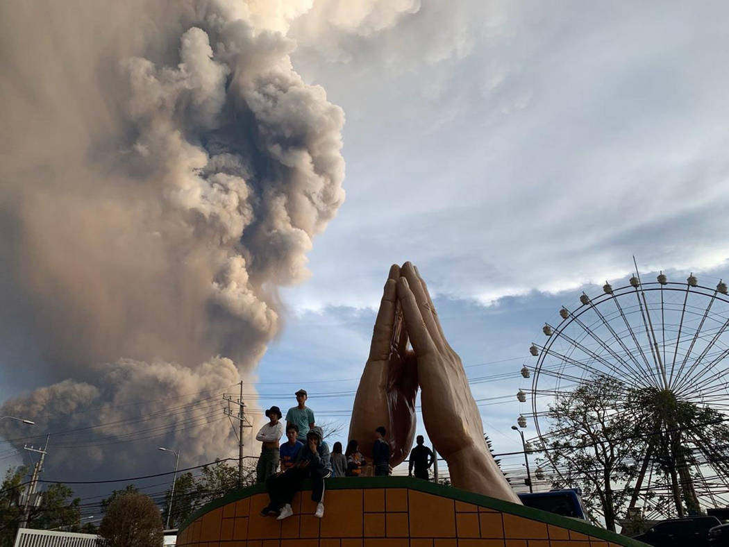 People watch as the Taal volcano spews ash and smoke during an eruption in Tagaytay, Cavite pro ...