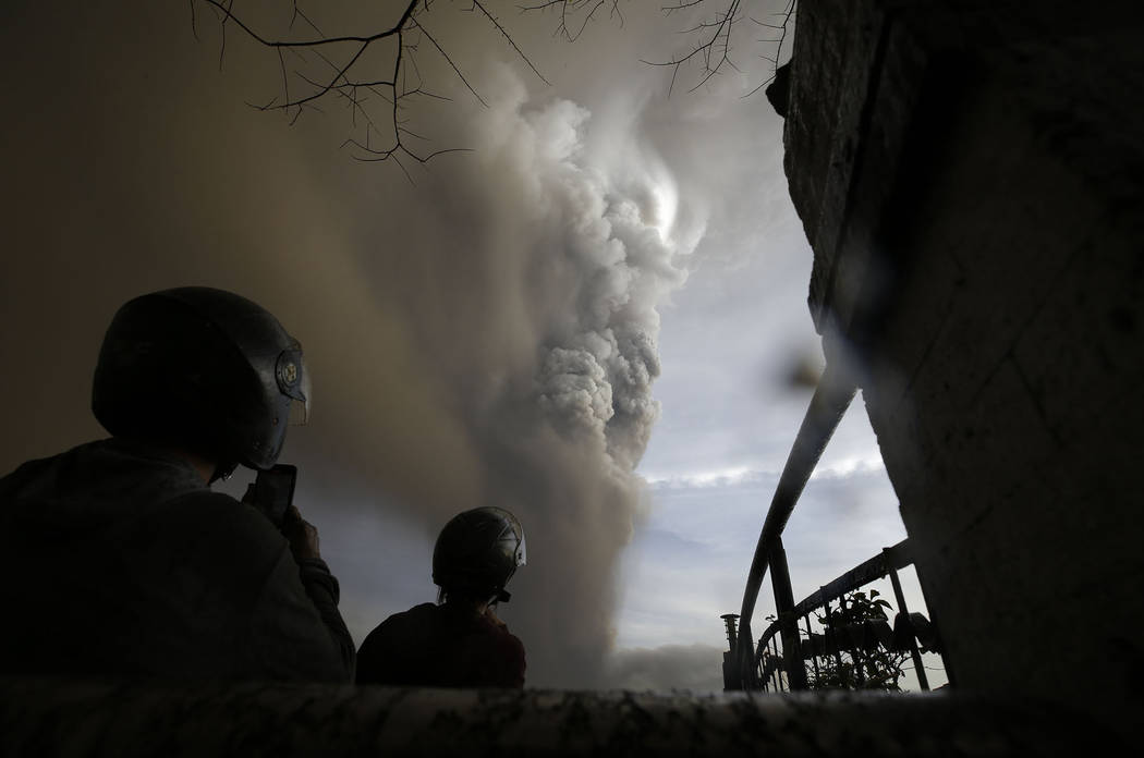 People watch as Taal Volcano erupts Sunday Jan. 12, 2020, in Tagaytay, Cavite province, outside ...
