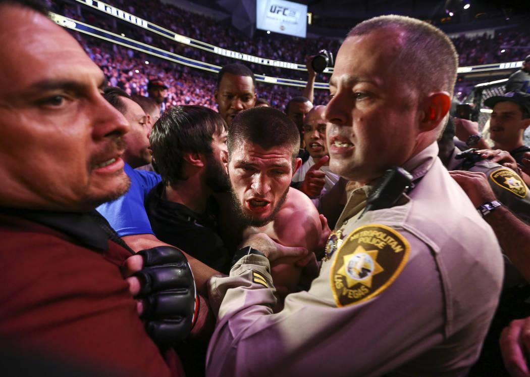 Fighter Khabib Nurmagomedov is held back by Las Vegas police and security following Nurmagomedo ...
