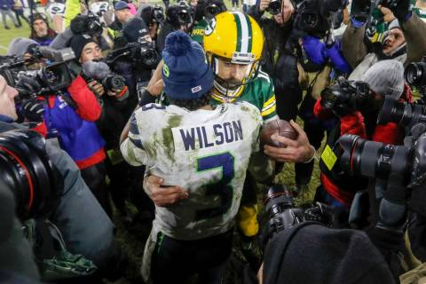 Green Bay Packers' Aaron Rodgers talks to Seattle Seahawks' Russell Wilson after an NFL divisio ...
