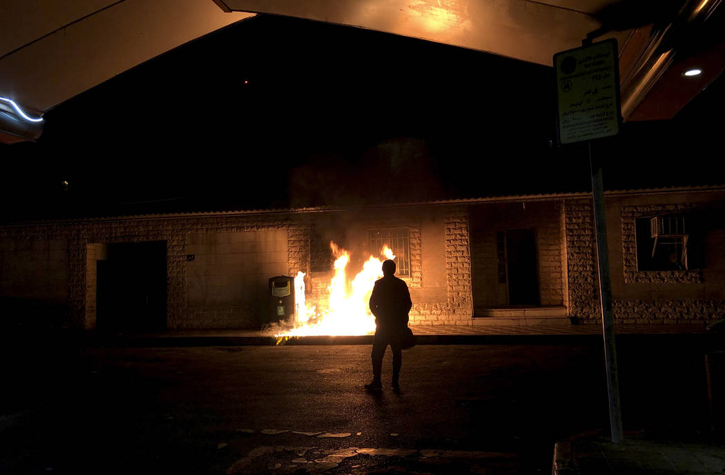 In this photograph taken Sunday, Jan. 12, 2020, a man stands in front of a fire set amid demons ...