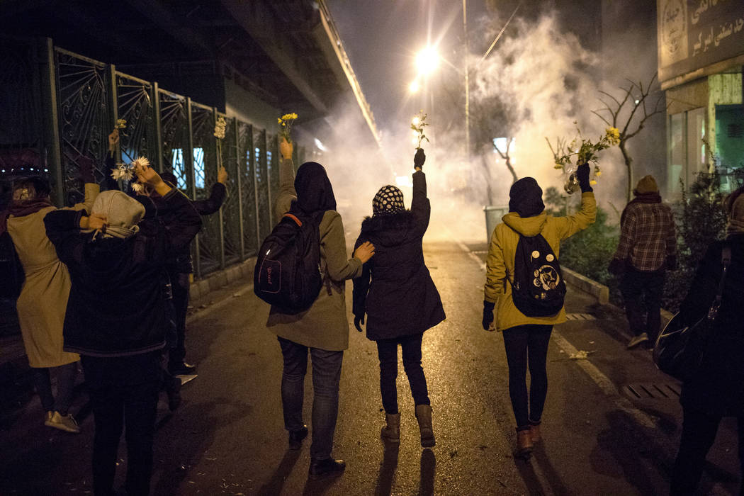 In a photograph taken Saturday, Jan. 11, 2020, protesters hold flowers as tear gas fired by pol ...