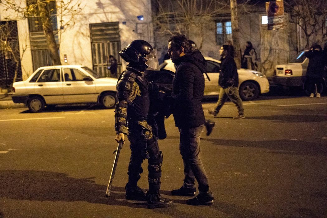 In this photograph taken Saturday, Jan. 11, 2020, a protester confronts an Iranian police offic ...