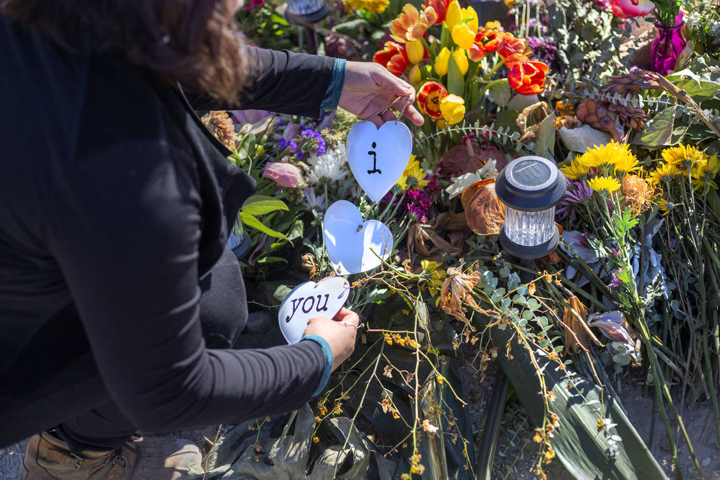 Ruth Neall organizes and puts fresh flowers on Monday, Jan. 13, 2020, at the memorial at the sp ...