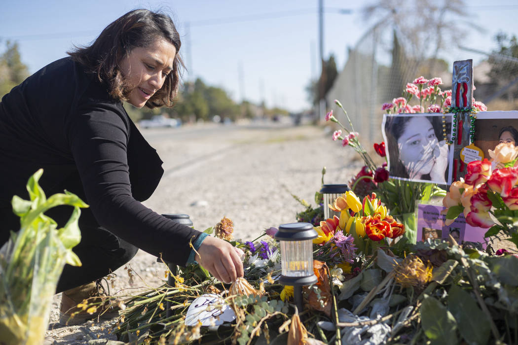 Ruth Neall puts fresh flowers at the memorial on Monday, Jan. 13, 2020, at the spot where her m ...