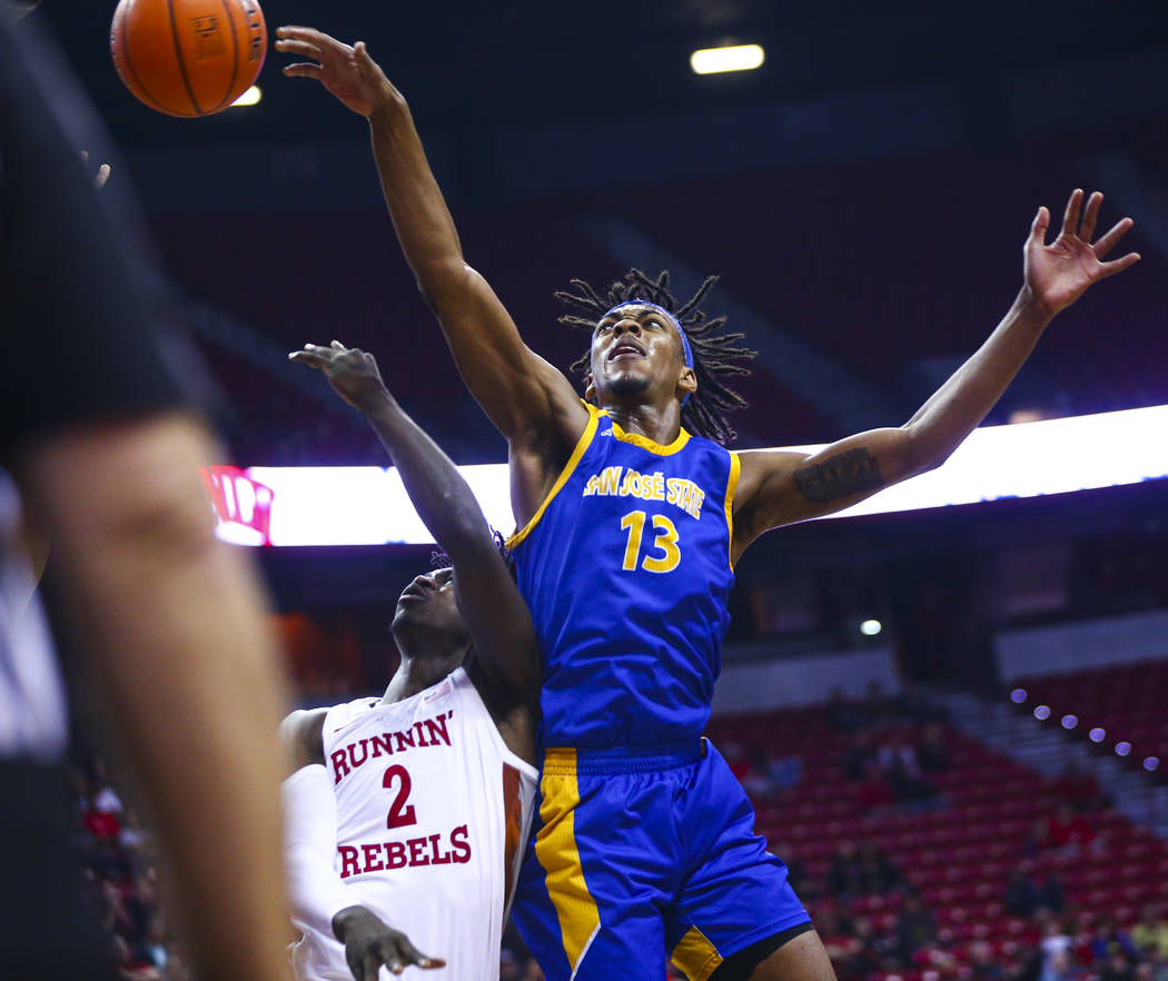 UNLV Rebels' Donnie Tillman (2) gets fouled by San Jose State Spartans' Seneca Knight (13) duri ...