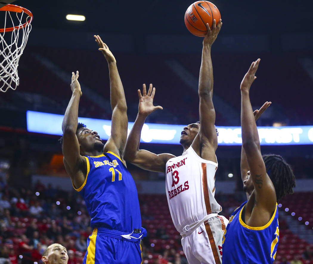 San Jose State Spartans' Christian Anigwe (11) and Seneca Knight (13) defend as UNLV Rebels' Br ...
