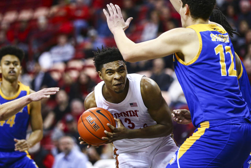 UNLV Rebels' Bryce Hamilton (13) moves the ball under pressure from San Jose State Spartans' Ed ...