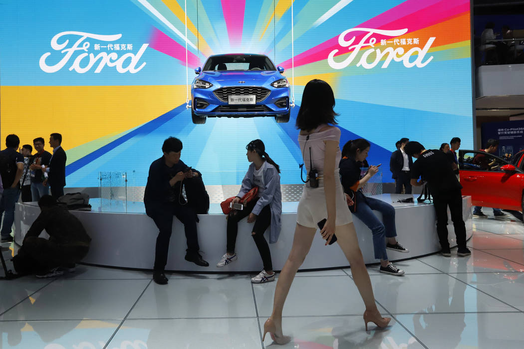 FILE - In this April 25, 2018, file photo, attendees visit the Ford booth during Auto China 201 ...