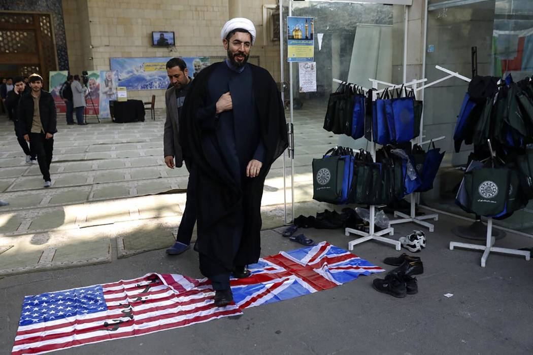 A cleric walks on the U.S. and British flags while leaving a gathering to commemorate the late ...