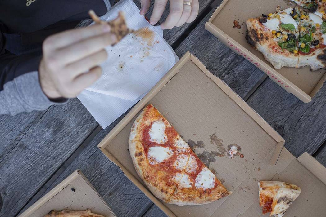 A Custom Pizza Truck costumer eats the Salami Gorgonzola pizza outside of the food truck on Thu ...