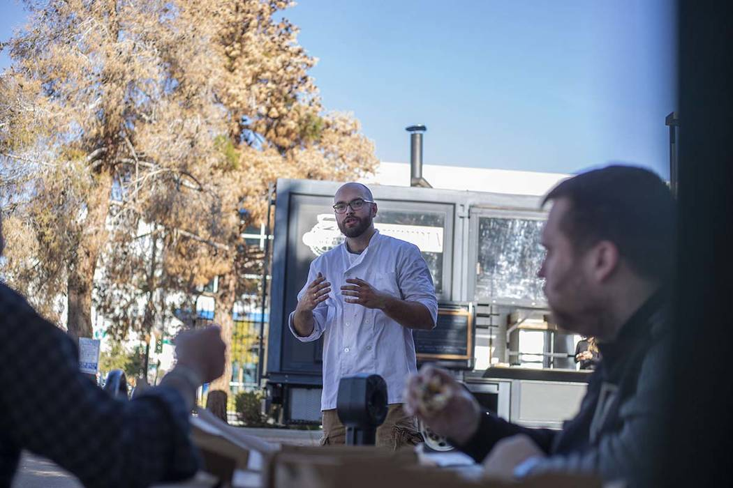 Chef Bartosz Wawrzyszak, owner of the Custom Pizza Truck, shares his story to costumers outside ...