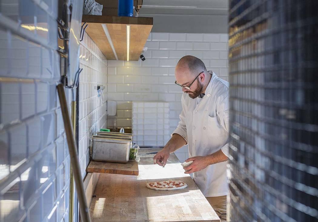 Chef Bartosz Wawrzyszak, owner of the Custom Pizza Truck, places gorgonzola on dough in his foo ...