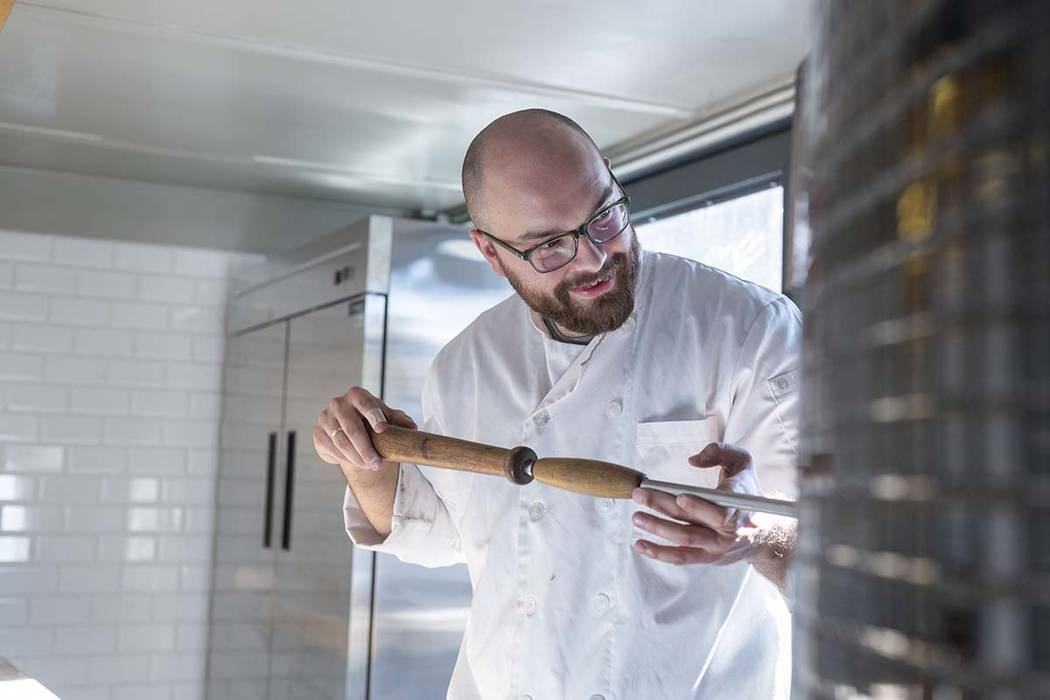 Chef Bartosz Wawrzyszak, owner of the Custom Pizza Truck, makes a pizza in his food truck on Th ...