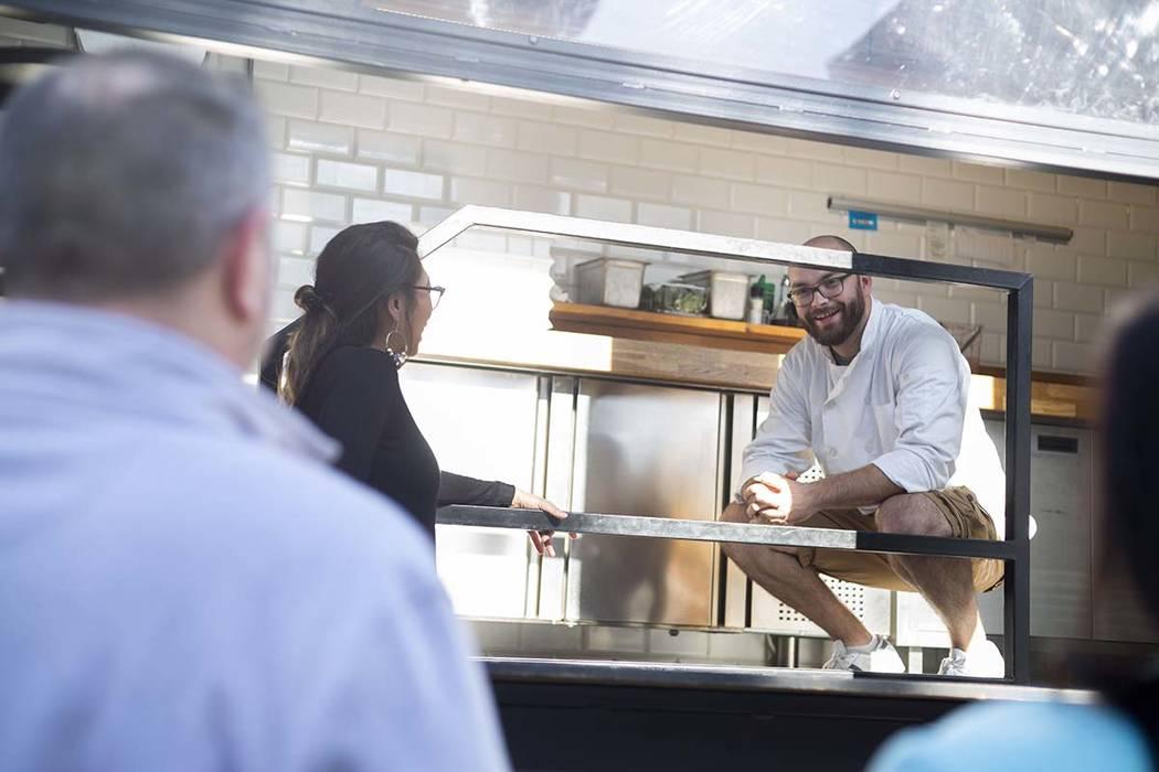 Rachelle Luna, left, and Chef Bartosz Wawrzyszak, owner of the Custom Pizza Truck, speak to cos ...