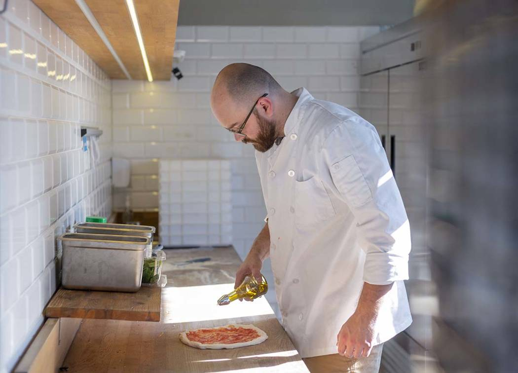 Chef Bartosz Wawrzyszak, owner of the Custom Pizza Truck, drizzles olive oil onto dough while m ...