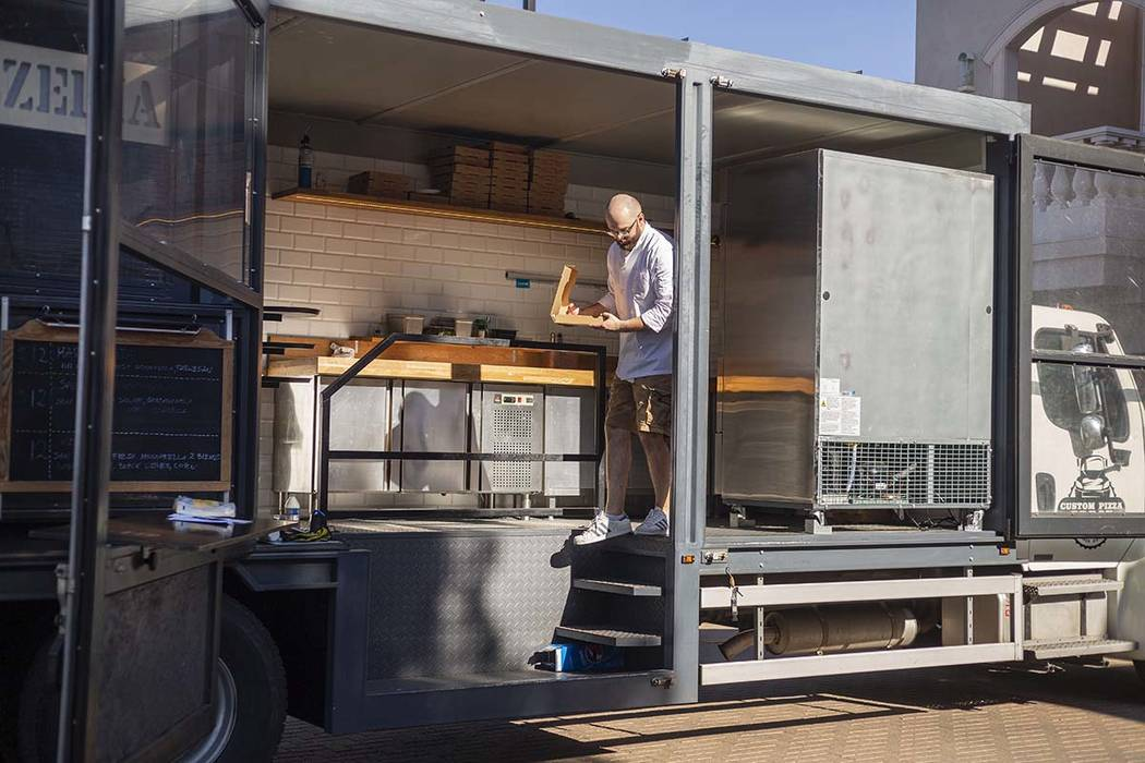 Chef Bartosz Wawrzyszak, owner of the Custom Pizza Truck, delivers a pizza to a customer from h ...