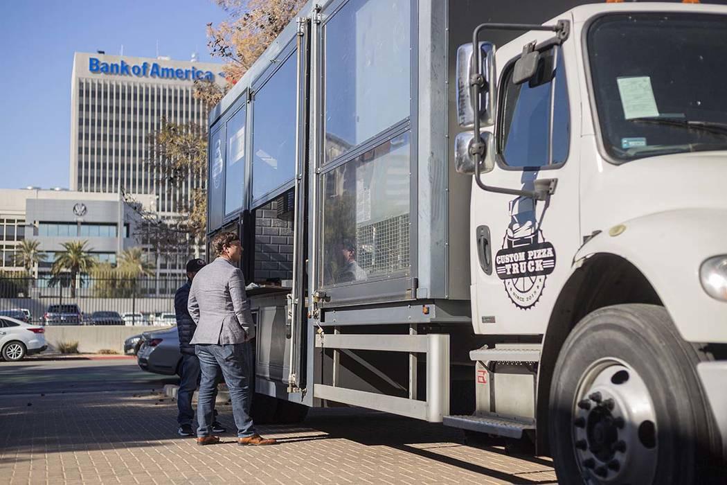 Elliott Schlottman of Las Vegas orders from Custom Pizza Truck, parked on 317 S. Sixth St., in ...