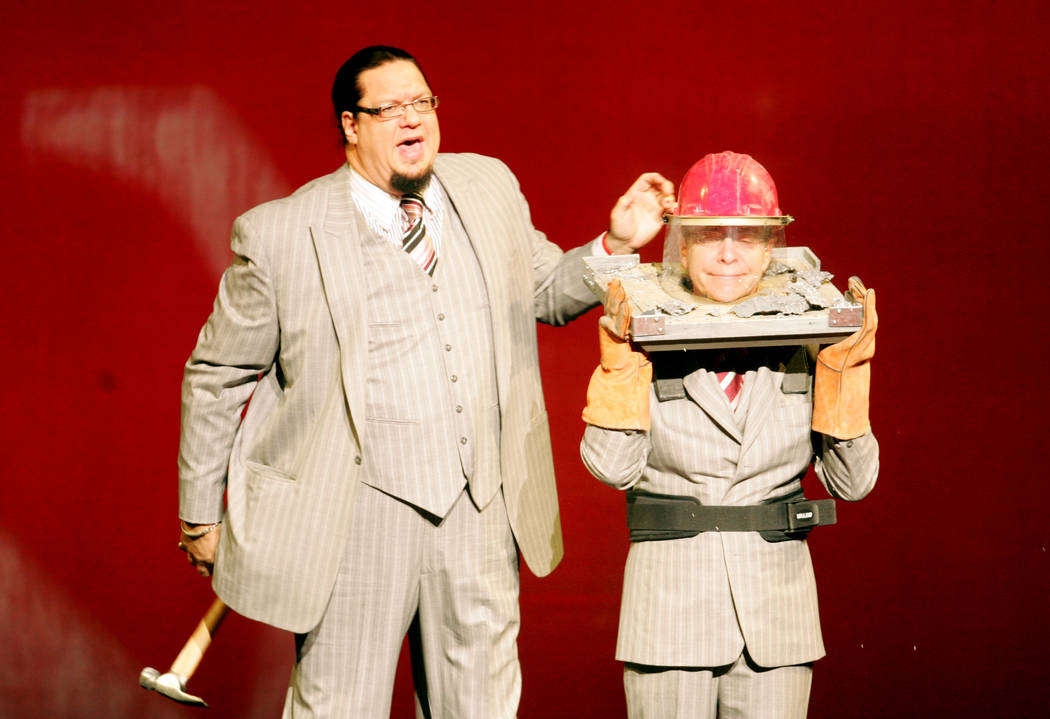 """Comedic illusionists Penn Jillette, left, and Teller perform an illusion during their """"Penn & T ..."""