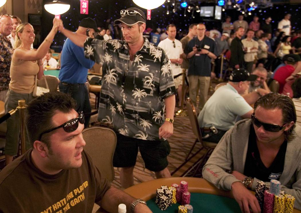 """Poker player Bobby Law 'high fives"""" his wife Kecia after winning a pot at the World Series of P ..."""