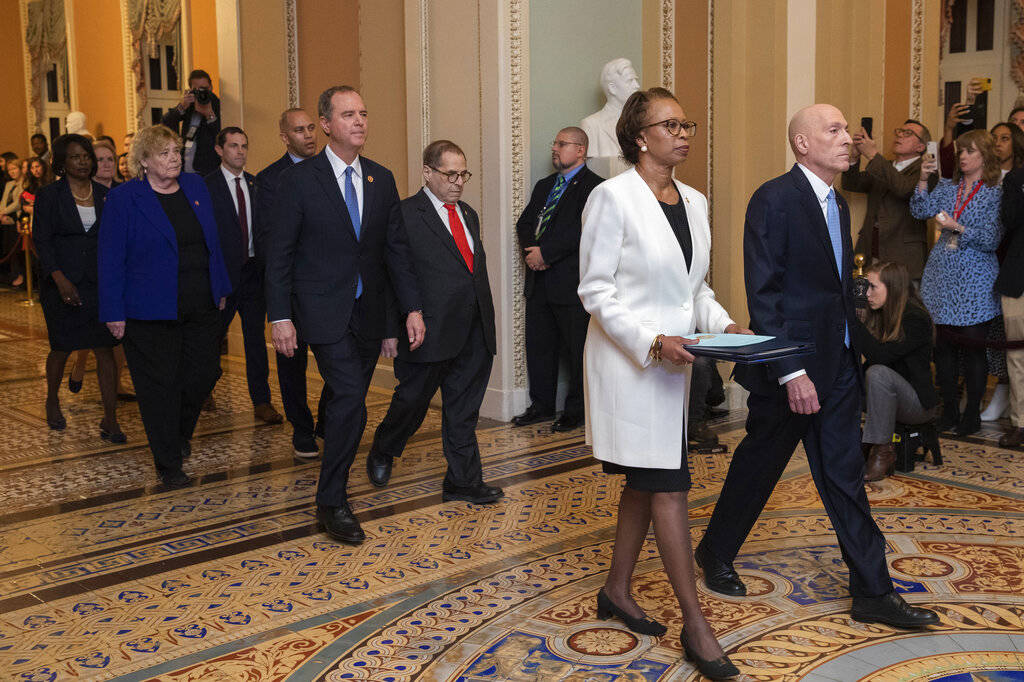 House Sergeant at Arms Paul Irving and Clerk of the House Cheryl Johnson carry the articles of ...