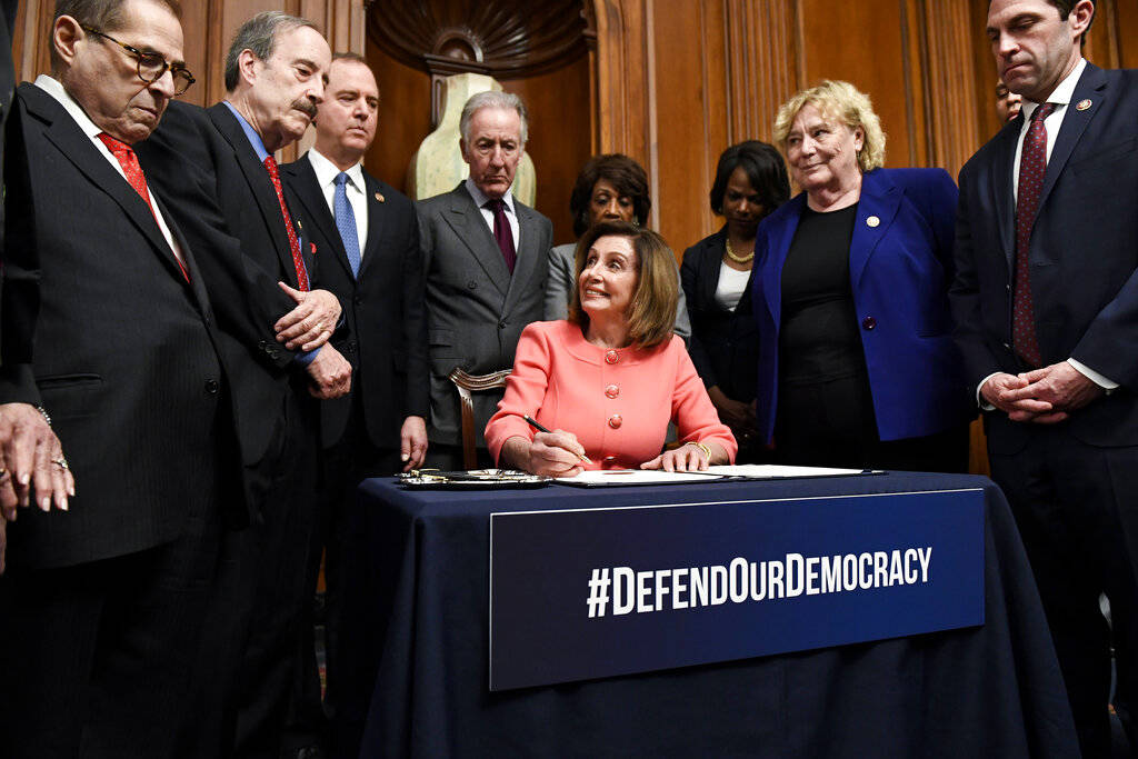 Speaker of the House Nancy Pelosi, D-Calif., signs the articles of impeachment during an engros ...