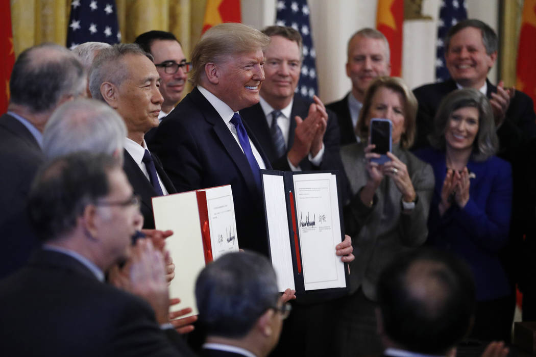 President Donald Trump, center, and Chinese Vice Premier Liu He, left, hold the U.S. China Trad ...