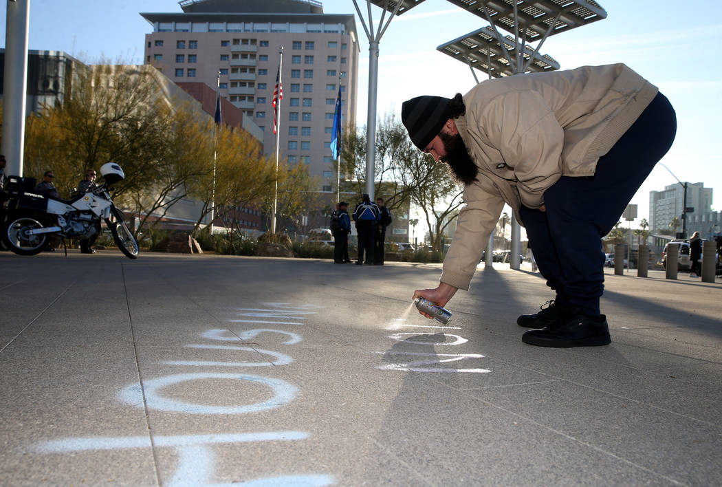 Joey Lankowski of Las Vegas uses sidewalk chalk spray before the start of a Las Vegas City Coun ...