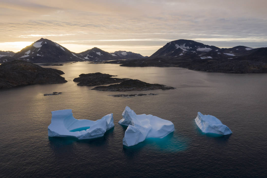 FILE - In this Aug. 16, 2019, file photo, large icebergs float away as the sun rises near Kulus ...