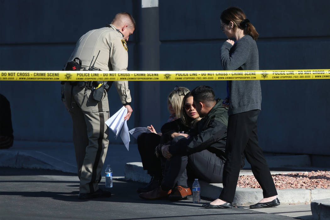 People wait as Las Vegas police investigate an officer-involved shooting that occurred in the 6 ...