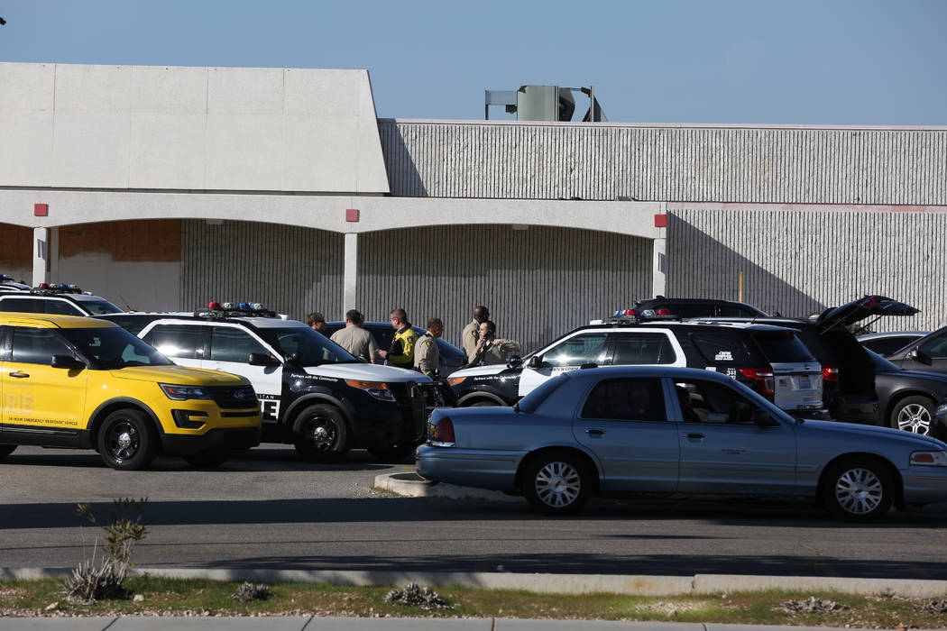 Las Vegas Metropolitan Police muster near an open field barricade with shooting suspect on Rain ...