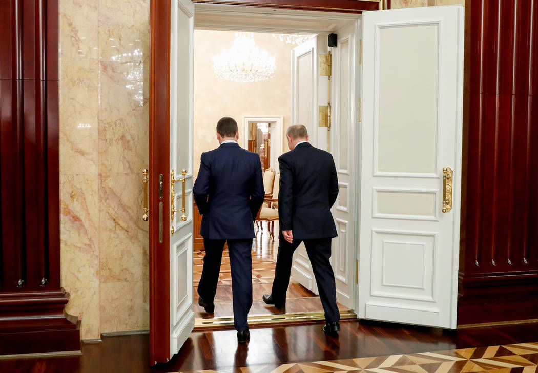 Russian President Vladimir Putin, right, and Russian Prime Minister Dmitry Medvedev leaves a ca ...