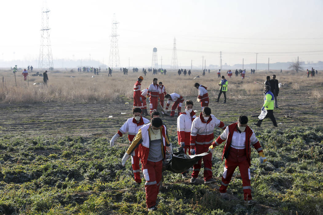 Rescue workers recover the bodies of victims of a Ukrainian plane crash in Shahedshahr, southwe ...