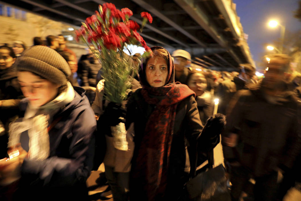People gather for a candlelight vigil to remember the victims of the Ukraine plane crash, at th ...