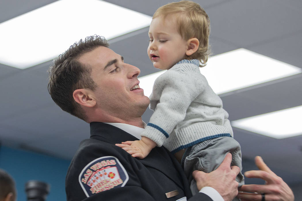 Las Vegas Fire and Rescue firefighter Justin Field holds his son, 1-year-old Levi Field, during ...