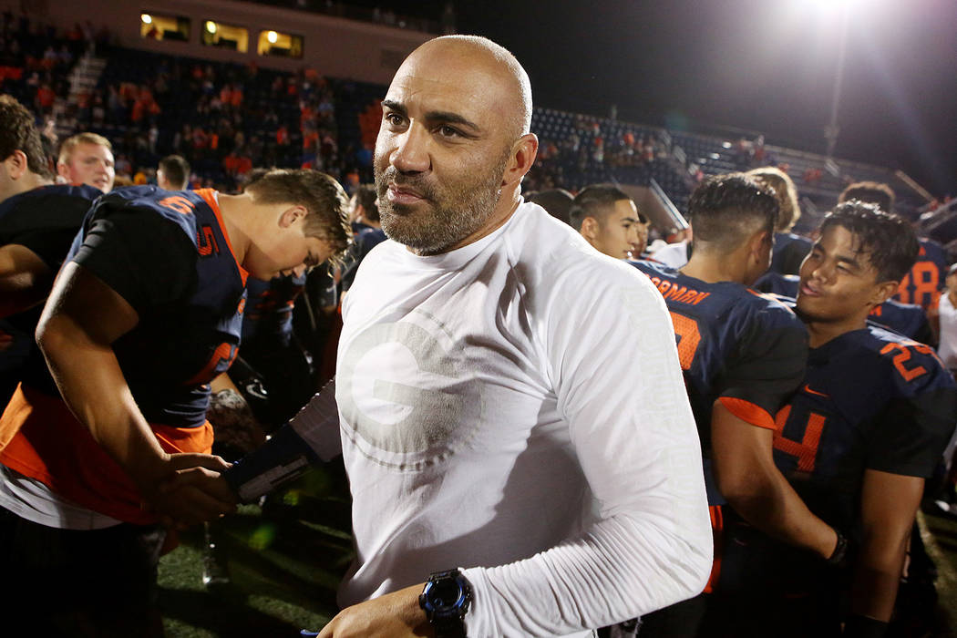 Bishop Gorman head coach Kenny Sanchez, center, shakes hands with players after their 34-7 win ...