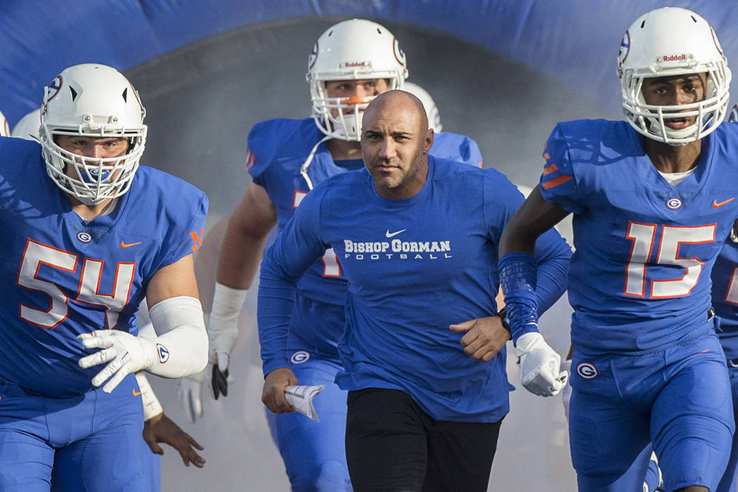 Bishop Gorman head coach Kenny Sanchez, middle, leads the Gaels onto the field before the start ...