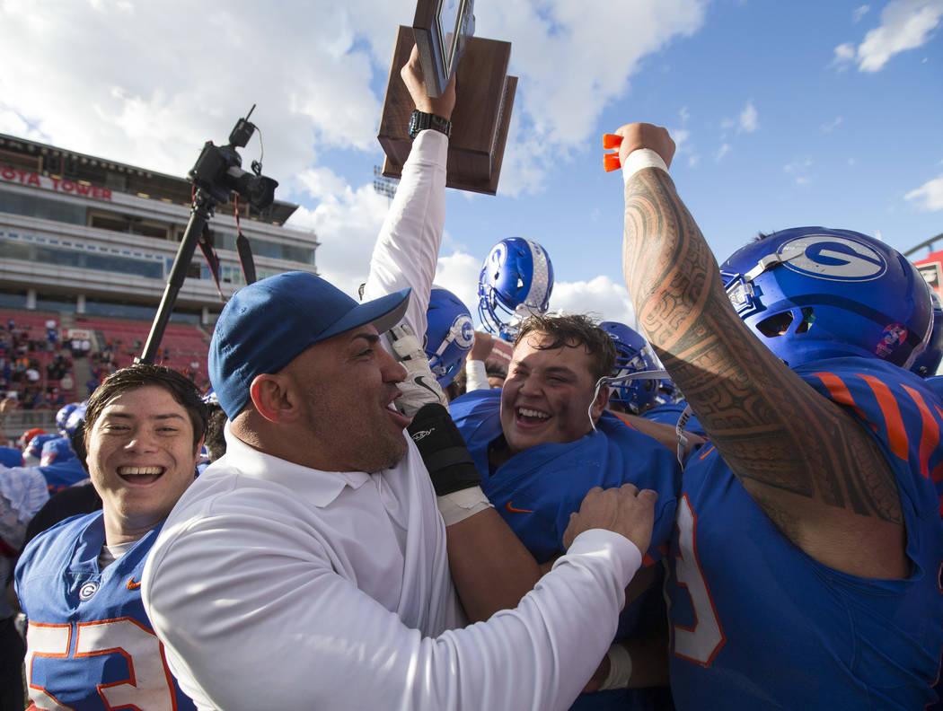 Bishop Gorman coach Kenny Sanchez and his players celebrate after defeating Reno's Bishop Manog ...