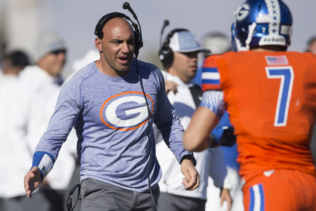 Bishop Gorman's head football coach Kenny Sanchez reaches his hand for Biaggio Walsh (7) after ...