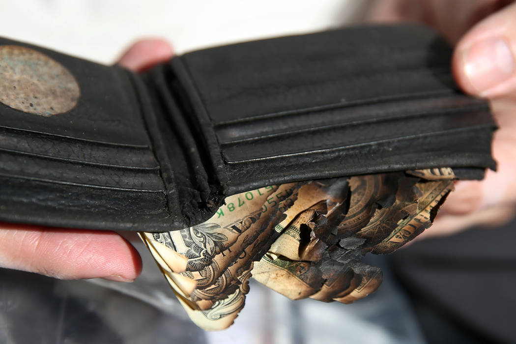Scott Booth, a former pilot for Papillon Grand Canyon Helicopters, shows his charred wallet at ...