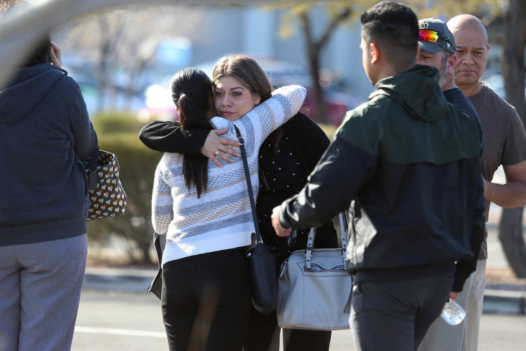 People embrace after leaving the scene of an officer-involved shooting that occurred in the 690 ...