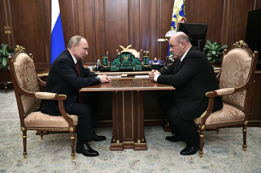Russian President Vladimir Putin, left, listens to Tax Service chief Mikhail Mishustin during t ...