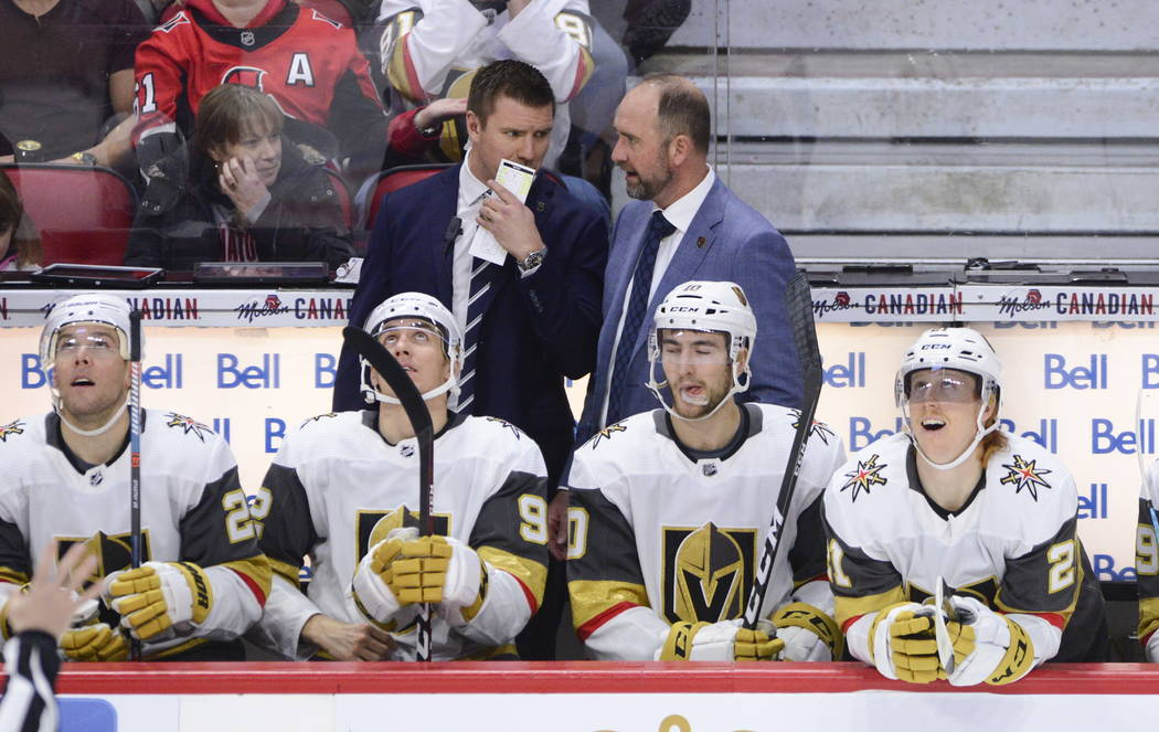 Vegas Golden Knights new head coach Peter DeBoer talks to one of his coaches on the bench as th ...