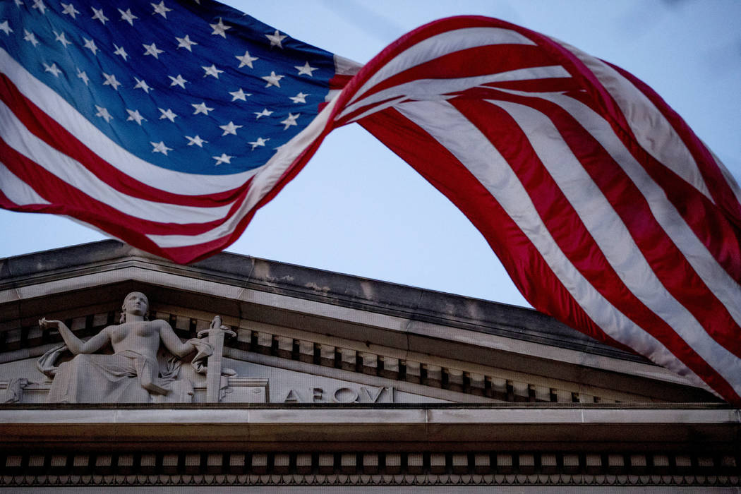 FILE - In this March 22, 2019 file photo, an American flag flies outside the Department of Just ...