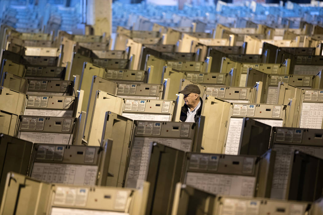 FILE- In this Oct. 14, 2016, file photo, a technician works to prepare voting machines to be us ...