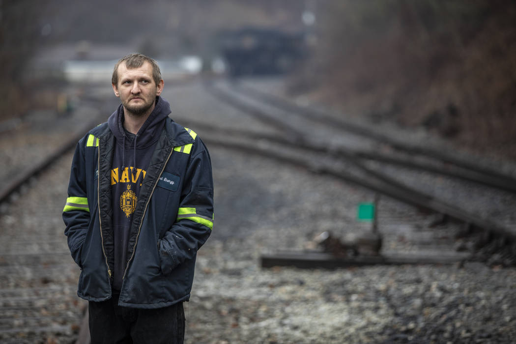 In this Tuesday, Jan. 14, 2020 photo, Timmy George, an employee of Quest Energy, stands on rail ...