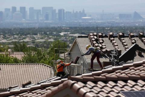 Construction workers set bundles of tile on the roof of an under-construction house in the mast ...